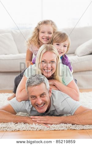 Portrait of playful family lying on each other in living room