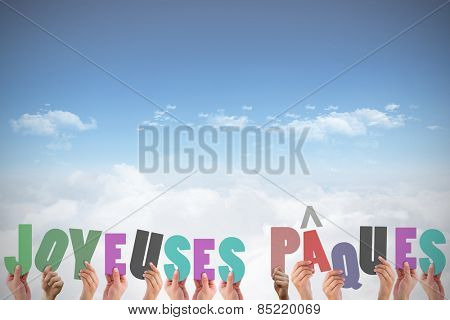 Hands holding up joyeuses pasques against bright blue sky over clouds