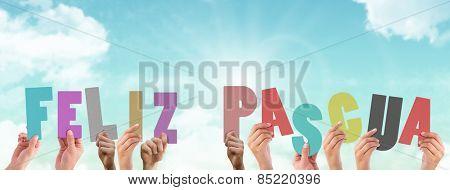 Hands holding up feliz pasqua against blue sky