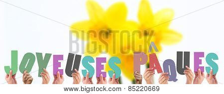 Hands holding up joyeuses pasques against pretty yellow daffodils with copy space