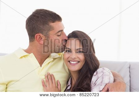 Portrait of happy woman being kissed by man at home