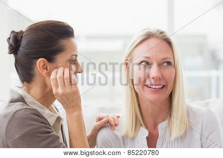 Women gossiping at home in living room
