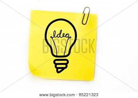 Light bulb against sticky note with grey paperclip