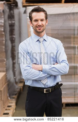 Smiling manager with arms crossed in warehoused