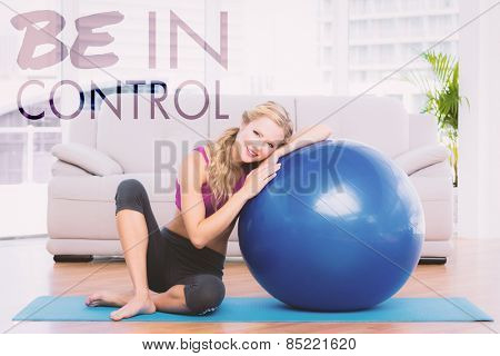 Toned blonde sitting beside exercise ball smiling at camera against be in control