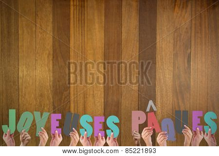 Hands holding up joyeuses pasques against wooden surface with planks
