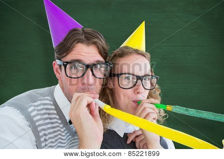 Geeky hipster couple blowing party horn against green chalkboard