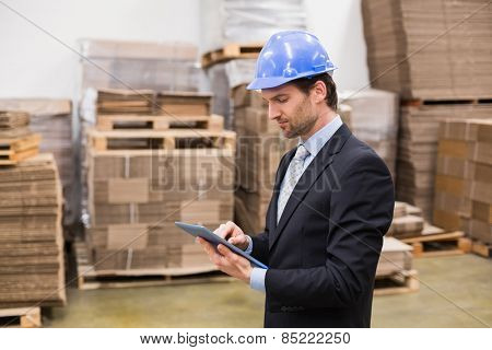 Warehouse manager wearing hard hat using tablet in a large warehouse
