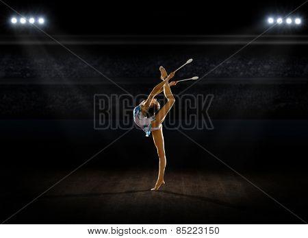 Girl engaged art gymnastics at sports hall
