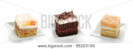 Three Single Cakes With Fruit, Jelly, Chocolate And Cream, Group Of Dessert Cuts, Isolated On White Background