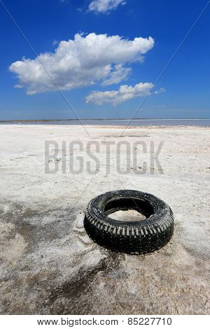 Abandoned old tyre on salt sea shore