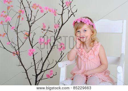 Girl In A Wreath Of Flowers In Pink Dress Sitting On A Chair Smiling, Hand Propping Cheek