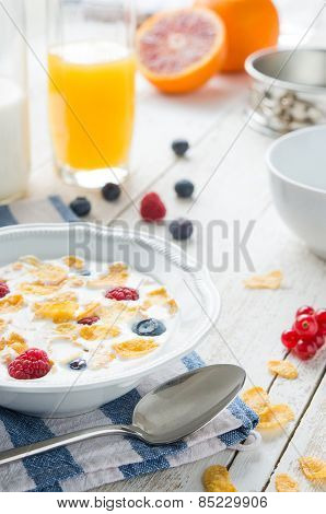 A glass of orange juice and a bowl of milk with cornflaks and fruit on a rusti table