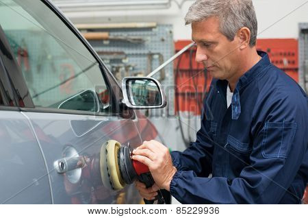 Portrait Of Mature Auto Mechanic Polishing Car At Workshop