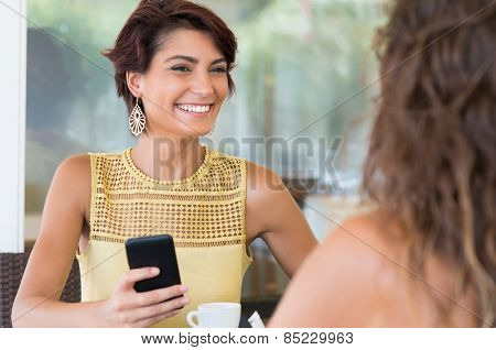 Two Young Female Friends Chatting With Each Other At Coffee Bar