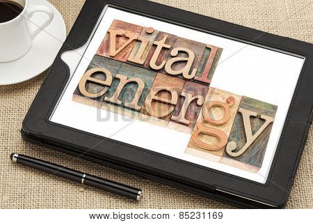vital energy typography - text in letterpress wood type blocks on a digital tablet with cup of coffee