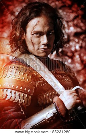 Close-up portrait of the ancient male warrior in armor holding sword. Historical character. Fantasy.