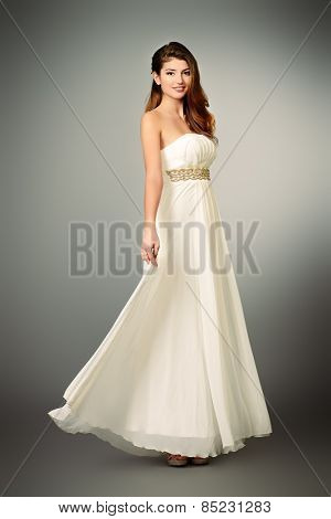 Full length portrait of a charming beautiful girl in elegant long white dress. Fashion shot.