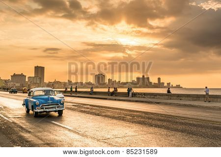 HAVANA,CUBA - MARCH 5, 2014 : Vintage american car at the Malecon avenue during a beautiful sunset