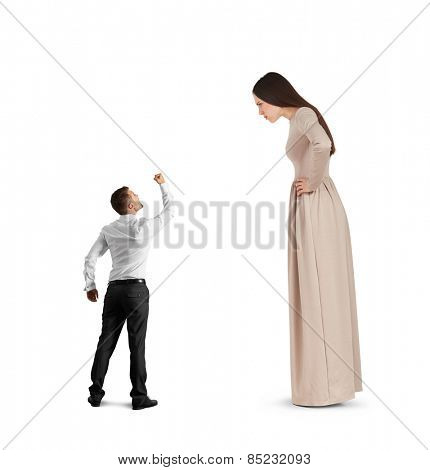 angry small man waving his fist, screaming and looking at big serious woman in long dress. isolated on white background
