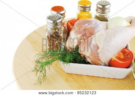 uncooked chicken drumstick and different spices on wood