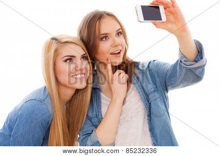 Young beautiful female friends making a selfie