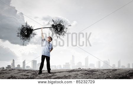 Boy of school age lifting barbell on one hand