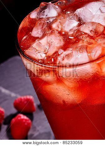 Red berry and cold drink  with cube ice on dark background. Close up.
