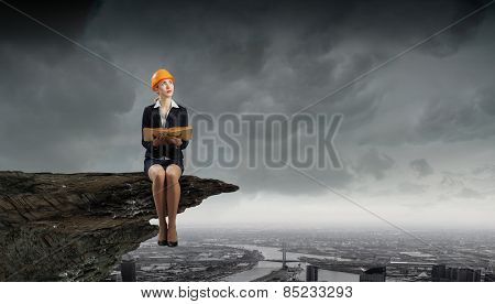 Young woman in hardhat sitting on top of rock with book