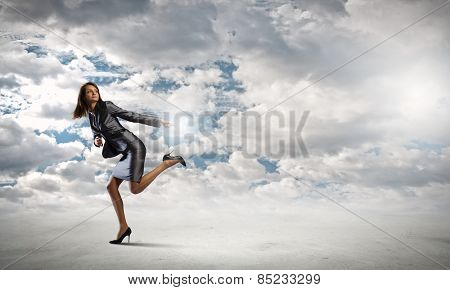 Young pretty businesswoman in suit running away
