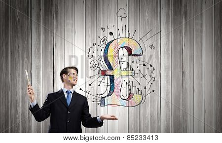 Young handsome businessman holding pound symbol in palm