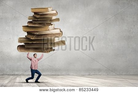 Young guy carrying pile of old books