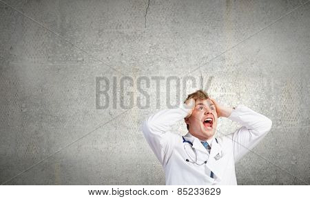 Young frustrated crazy doctor screaming very emotionally