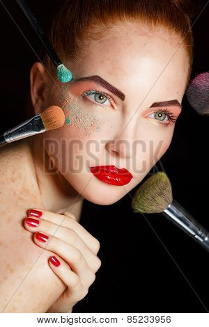 Beautiful woman with makeup brushes near her face