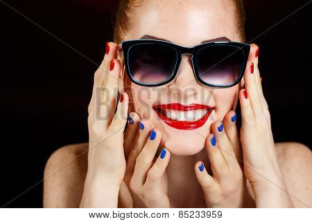 Beautiful young model with red lips and red manicure on black background