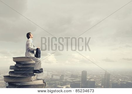 Young man sitting on pile of old books