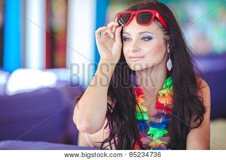 Beautiful brunette in a bikini under a canopy resting on the beach.