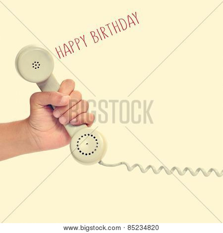 the hand of a young man holding the handset of a retro telephone and the text happy birthday on a beige background, with a retro effect