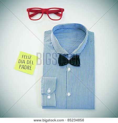 high-angle shot of a table with a pair of eyeglasses, a bow tie and a shirt, and a sticky note with the text feliz dia del padre, happy fathers day in spanish written in it