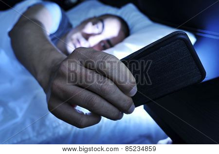 closeup of a young man in bed looking at the smartphone at night