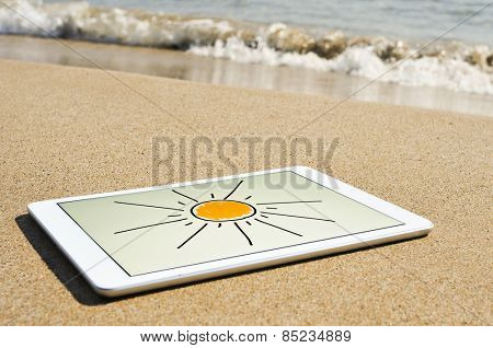 a sun drawn in a tablet computer, in the sand of a beach