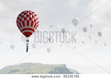 Businessman flying on aerostat balloon high in sky