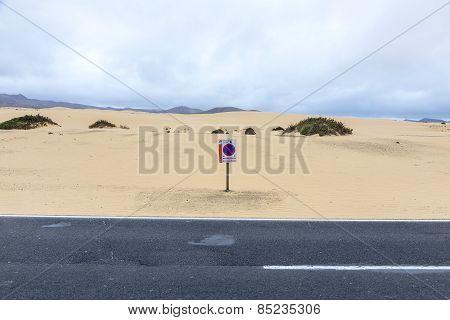 Desert Road In Fuerteventura With Parking Forbidden Sign In The Dunes