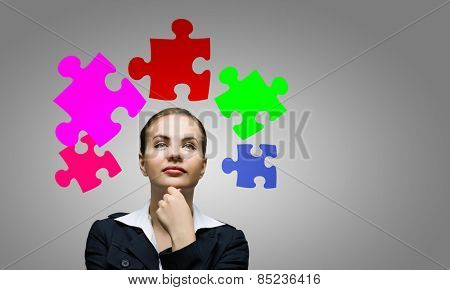 Young attractive woman and colorful puzzles above her head