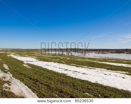 A field in spring with the remnants of snow on a sunny day