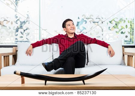 Asian Korean man sitting on sofa in furniture store