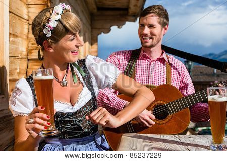 Couple on mountain hut in the Alps making guitar music and drinking wheat beer
