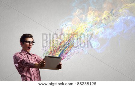 Young man looking with shock in tablet pc