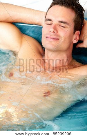 Young man relaxing in hot tub. Summer vacation.