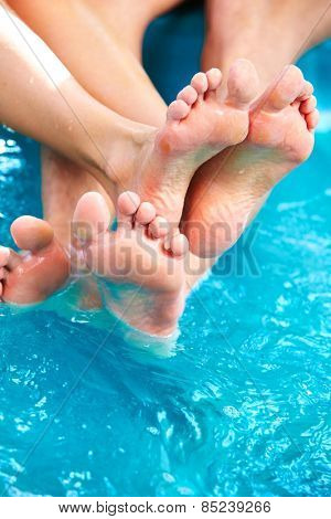 People feet relaxing in hot tub. Summer vacation.